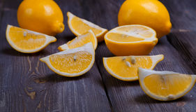 Low key lemons. Some sliced lemons on a wooden table Stock Photos