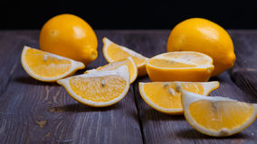 Low key lemons. Some sliced lemons on a wooden table Royalty Free Stock Photo