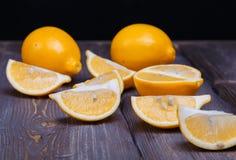 Low key lemons. Some sliced lemons on a wooden table Stock Image