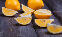 Low key lemons. Some sliced lemons on a wooden table Royalty Free Stock Photography