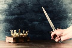Low key photo of gold crown and king holding sword. fantasy medieval period. Low key photo of gold crown and king holding sword. fantasy medieval period stock photography