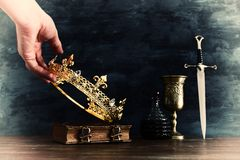 Low key photo of king holding gold crown and sword. fantasy medieval period. Low key photo of king holding gold crown and sword. fantasy medieval period stock photo
