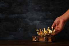 Low key photo of king holding gold crown and sword. fantasy medieval period. Low key photo of king holding gold crown and sword. fantasy medieval period royalty free stock image