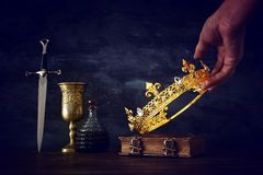Low key photo of king holding gold crown and sword. fantasy medieval period. Low key photo of king holding gold crown and sword. fantasy medieval period stock images