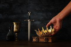 Low key photo of king holding gold crown and sword. fantasy medieval period. Low key photo of king holding gold crown and sword. fantasy medieval period stock image