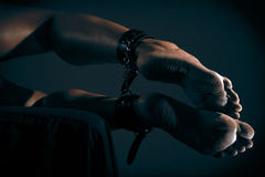 Low key photo of sexy female nude legs binded with cuffs against dark background Royalty Free Stock Image