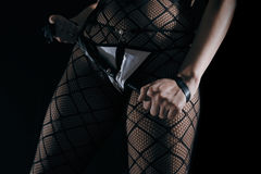 Low key photo of sexy female nude legs in fetish nett tights and g-string tongs panties holding whip in hands Stock Photography