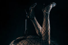 Low key photo of sexy female nude legs in fetish nett tights and high heels shoes holding whip against dark background Stock Image