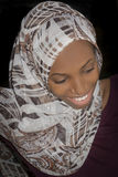 Low key portrait of a beautiful Afro girl wearing a headscarf and smiling Stock Image