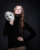 Low key portrait of a beautiful woman holding mask Stock Photo