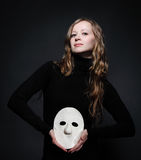 Low key portrait of a beautiful woman holding mask Stock Photography
