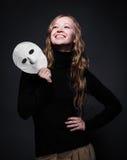 Low key portrait of a beautiful woman holding mask Stock Photo