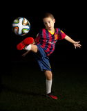Low key portrait of a boy kicking a world cup football Royalty Free Stock Photo