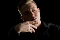 Low key portrait of contemplative young man looking aside. Low-key close up portrait of young serious man in dark shirt with hand at chin looking aside Stock Photo