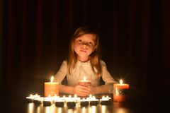 The cute little blonde girl holds a burning candle. Lots of candles are around her, over dark background stock images