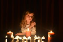 The cute little blonde girl keeps her hand on her shoulder and she is looking at the burning candle. Lots of candles are around h stock photo