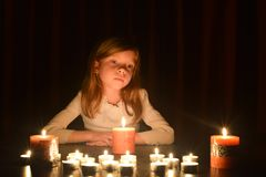The cute little blonde girl is looking on the light of candle. Lots of candles are around her, over dark background royalty free stock photos