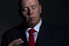 Low key portrait of man with glasses and eyes cosed. Low key portrait of a mature bald headed male wearing a suit, He has his eyes closed and the arms of teh stock image