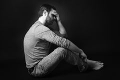 Low key portrait of man sitting in dark and Stock Images