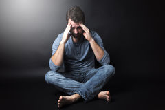 Low key portrait of man sitting in dark and Royalty Free Stock Images