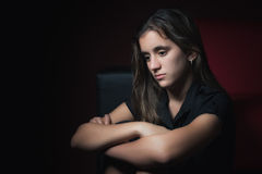 Low key portrait of a sad teenage girl. With a thoughtful and worried expresion Royalty Free Stock Photo