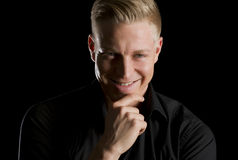 Low key portrait of smiling seductive man looking straight. Stock Images