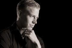 Low key portrait of young attractive man, black and white. Black and white portrait of smiling handsome man in dark shirt with hand at chin looking aside, low Royalty Free Stock Image