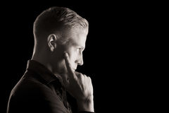 Low key profile portrait of young man, black and white. royalty free stock images