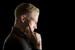 Low key profile portrait of young serious man. Royalty Free Stock Images