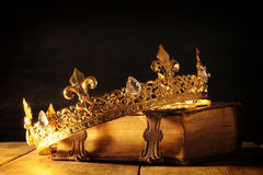 Low key of queen/king crown on old book. vintage filtered. fantasy medieval period. Low key image of beautiful queen/king crown on old book. vintage filtered stock photos