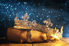 Low key of queen/king crown on old book. vintage filtered. fantasy medieval period. Low key image of beautiful queen/king crown on old book. vintage filtered stock photo