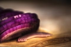 Low Key Red Onion Slices. Red onion slices on wood cutting board stock image