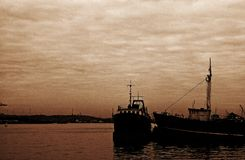 SEPIA IMAGE OF SHIPS IN THE HARBOUR. Low key sepia image of ships at anchor in the harbour under overcast sky Royalty Free Stock Images
