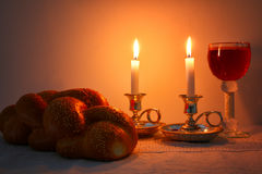 Low key shabbat image. challah bread, shabbat wine and candelas. On wooden table Royalty Free Stock Images