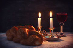 Low key shabbat image. challah bread, shabbat wine and candles. On wooden table Stock Photo