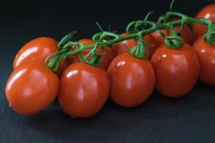 Low key shot of tomatoes lying on the black table Stock Photos