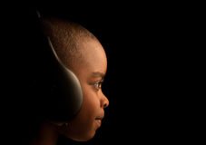 Low key sound. A low key image of a a child with headphones on Royalty Free Stock Photo