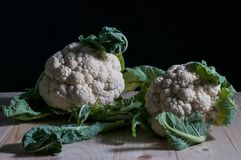 Cauliflowers on a wooden table. Low key still life with two cauliflowers on a wooden table Stock Photography