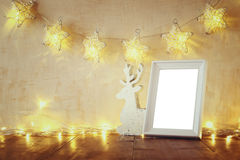 Low key and vintage filtered image of wooden reindeer and blank frame with garland warm lights. template ready to put photography. Stock Image