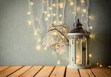 Low key white wooden vintage lantern with burning candle and tree branches on wooden table. retro filtered image . Stock Images