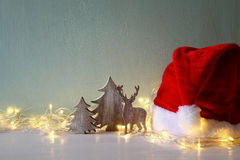 Low key of wooden christmas tree and deer next to santa hat Royalty Free Stock Images
