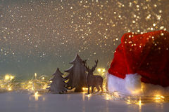 Low key of wooden christmas tree and deer next to santa hat Stock Photos