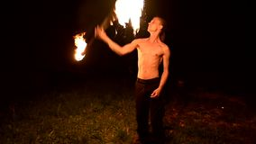 Low key. Young male with long hair and bare torso rotates burning torch outdoors on a black night video slow motion. Modern fakir does tricks with a burning stock video