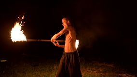 Low key. Young male with long hair and bare torso rotates burning torch outdoors on a black night video slow motion. Modern fakir does tricks with a burning stock footage