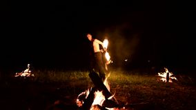 Low key. A young male with long hair and a naked torso rotates a burning torch outdoors on a black night video slow. Motion near the fires. Modern fakir does stock video