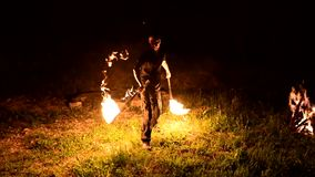 Low key. Young male with long hair rotates burning torch outdoors on a black night video slow motion. Modern fakir does. Tricks with a burning staff next to stock video footage