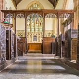 Low level distant view of the altar at Crowcombe church in Somerset. Showing the intricately carved altar rail, polished floor and the stained glass window stock photography