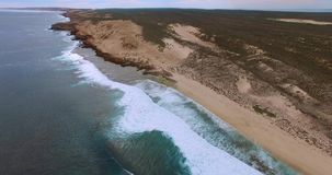 Low level flight along beach with large breaking waves to distant cliffs - Dirk Hartog Island, Shark Bay World Heritage Area. Low level aerial video of massive stock footage