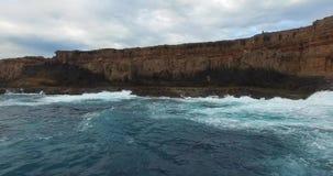 Low level flight over waves towards cliffs - Dirk Hartog Island, Shark Bay World Heritage Area. Low level aerial video over breaking waves towards the vertical stock footage