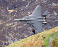 Low level jet. Low level F15 fighter jet flying past a person in the Mach Loop Royalty Free Stock Photos